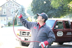 Owner Greg Pettis, administering some pest control with a Dominion Pest Control truck in the background.